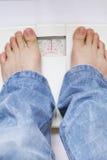 Füße auf Gewichtskala Stockbilder