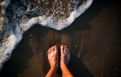 Füße auf Meersand und Wellen stockfotografie