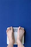 Füße auf Skala Stockfotografie