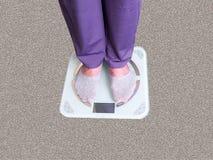 Füße auf Skalen auf Boden im Raum stockbilder