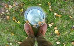 Füße bemannen das Gehen auf die Fallblätter, die mit Herbstsaisonnatur auf modischer Art der Hintergrund Lebensstil-Mode im Freie Lizenzfreies Stockfoto