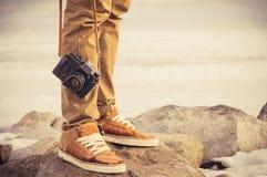 Füße bemannen und Retro- Fotokamera der Weinlese Lizenzfreie Stockfotos
