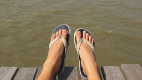 Füße blaues Gewebe Flip Flops auf hölzernem Dock tragend - sitzend im Sun lizenzfreies stockbild