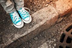 Füße in den blauen Schuhen stehen auf dem Straßenrand Lizenzfreies Stockfoto