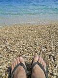 Füße in den Hefterzufuhren auf Pebble Beach Lizenzfreies Stockbild