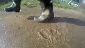 Füße in den schmutzigen Regenstiefeln führen eine Pfütze auf einem Schotterweg und heben spritzt an Langsame Bewegung stock video footage