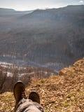 Füße in den Schuhen gelegt auf einen Felsen Lizenzfreies Stockfoto