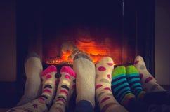 Füße in den Socken der ganzer Familie, die durch gemütliches Feuer sich wärmt Lizenzfreies Stockfoto