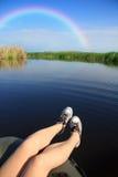 Füße in den Turnschuhen auf Fluss gestalten mit Regenbogen landschaftlich lizenzfreies stockbild