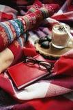 Füße in den warmen woolen Socken auf dem Bett Stockfotos