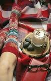 Füße in den warmen woolen Socken auf dem Bett Lizenzfreies Stockfoto
