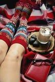 Füße in den warmen woolen Socken auf dem Bett Lizenzfreie Stockfotografie