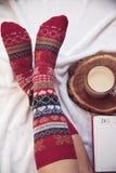 Füße in den warmen woolen Socken auf dem Bett Stockbilder