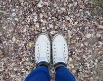 Füße in den weißen Turnschuhen Stockfotografie