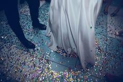 Füße der Braut und des Bräutigams auf einem Hintergrund von Konfettis lizenzfreie stockbilder