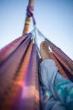 Füße in der bunten Hängematte Lizenzfreies Stockbild