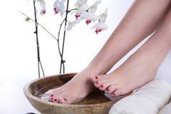Füße in der hölzernen Schüssel mit des Tuches und weißer Orchideenblume des Wassers und im Hintergrund lizenzfreie stockfotografie