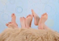 Füße der Kinder über Pelzdecke Lizenzfreie Stockbilder