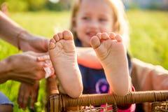 Füße der kleinen Mädchen, die in einem Weidenkorb an einem sonnigen Tag sitzen Stockfoto