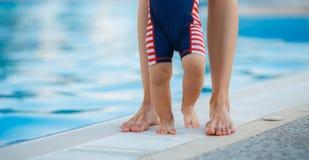 Füße der Mutter und des Kindes durch das Pool Stockfotografie
