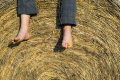 Füße des Kinderjungen sitzend auf Heuschober Stockfotos