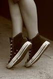 Füße des Mädchens in den gegenteiligen Turnschuhen (6) Stockfotografie