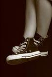 Füße des Mädchens in den gegenteiligen Turnschuhen (7) Stockfotografie