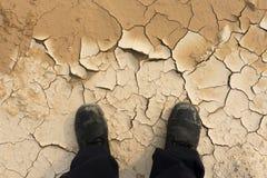 Füße des Mannes stehend auf trockenem Boden Stockbild