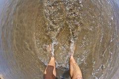 Füße des Mannes am Strand Stockbild
