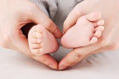 Füße des Mutterholdingschätzchens Stockfotografie