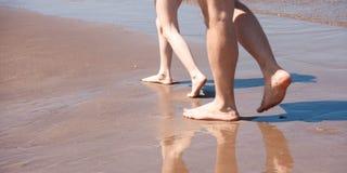 Füße des Vaters und des Kindes, die zusammen entlang die Küste gehen stockfoto