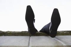 Füße, die über Wand baumeln stockfoto
