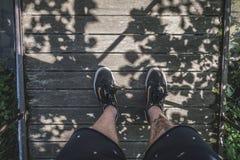 Füße, die auf der Holzbrücke stehen Lizenzfreies Stockbild