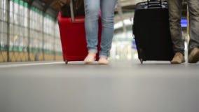 Füße, die auf die Plattformpassagiere mit einem Koffer, junge Paare gehend entlang die Plattform zum Zug mit gehen stock video