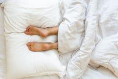 Füße, die auf weichem weißem Kissen am Bett liegen Lizenzfreies Stockfoto