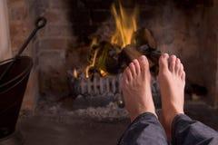 Füße, die an einem Kamin sich wärmen Lizenzfreie Stockfotos