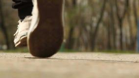 Füße, die entlang die Straße laufen