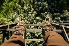 Füße, die von verlassenem Eisenbahngestell baumeln Lizenzfreie Stockfotos