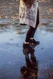 Füße einer Frau in einem Baumwollmantel, der auf Eis schiebt lizenzfreie stockfotos