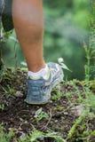 Füße einer jungen männlichen Person mit wandernde Schuhe während der Wanderung bis zum Berg im Schlamm Lizenzfreies Stockfoto