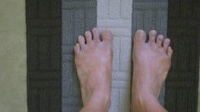 Füße einer kranke Mannübung auf der gerollten Yogamatte lokalisiert auf rustikalem Zementbodenhintergrund in einer Sporttätigkeit stock footage