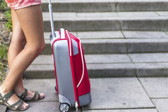 Füße eines jungen Mädchens nahe rotem Koffer Stockbild