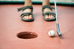 Füße eines Kindes, das Minigolf spielt Lizenzfreies Stockfoto