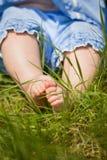 Füße eines kleinen Babys auf dem grünen Gras Sonniger Tag Nettes Kind, das aus den Grund sitzt Barfuß von einem Kind Lizenzfreie Stockfotos