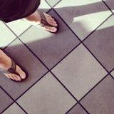 Füße, Flipflops und Fliesen Stockfoto