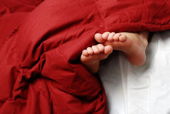 Füße im Bett Lizenzfreies Stockfoto