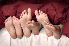 Füße im Bett Stockbilder