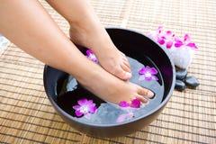 Füße im orientalischen Fußbad mit Blumen Stockfotografie