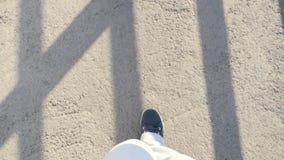Füße im Sport beschuht das Gehen auf Asphalt an der Brücke stock footage