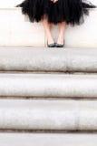 Füße junger Dame in einem Ballettröckchen, das über Treppe sitzt Lizenzfreie Stockfotografie